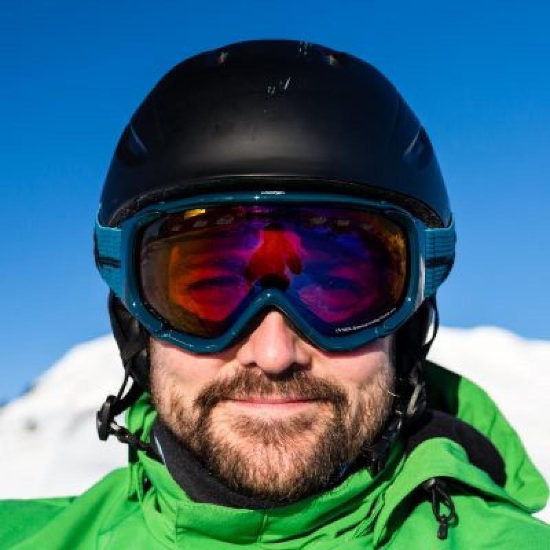 sciatore indossa maschera da sci con lente arancio specchiata blu