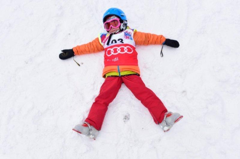 bambino indossa maschera da sci con lente arancio colore fucsia fluo